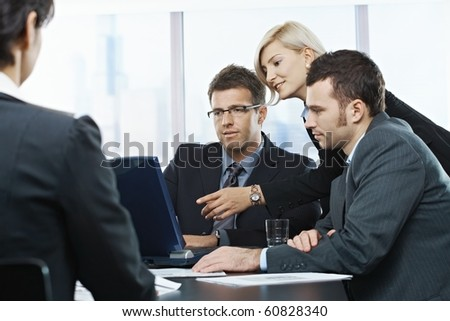 Businessmen looking at laptop, businesswoman pointing at screen in office, at meeting table