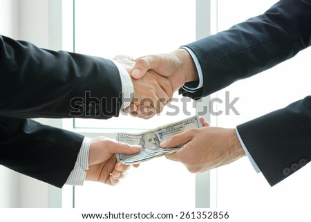 Businessmen making handshake while passing money - dealing & bribery concepts - stock photo