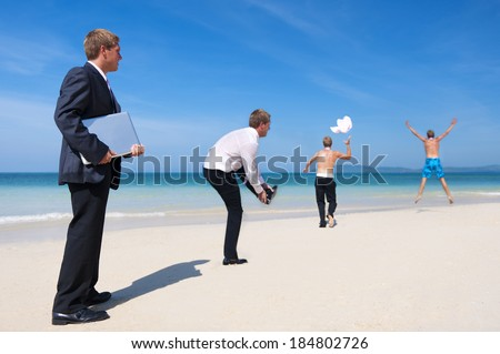 Businessmen Playing On The Beach - stock photo