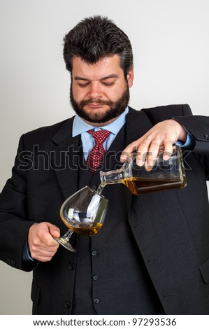 Businessmen pouring  a glass of whiskey - stock photo