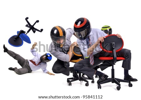 Businessmen racing in chairs with helmets - stock photo