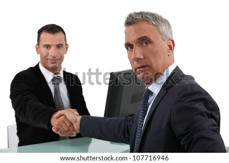 Businessmen sealing deal with hand shake - stock photo