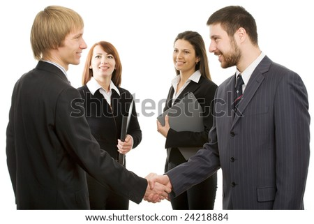 Businessmen shake their hands, two businesswomen look at them - stock photo