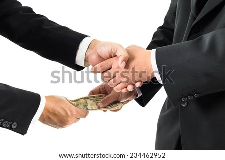 Businessmen shaking hands and receiving banknote - stock photo