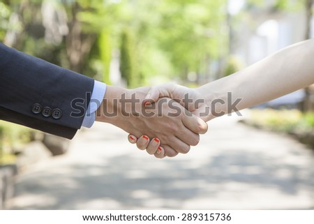 Businessmen shaking hands at business district - stock photo