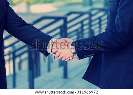 Businessmen shaking hands confidently. - stock photo