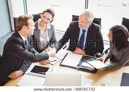Businessmen shaking hands in conference room in office - stock photo