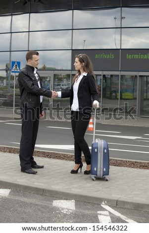 Businessmen shaking hands in front of a terminal - stock photo