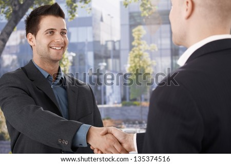 Businessmen shaking hands in front of office building, smiling. - stock photo