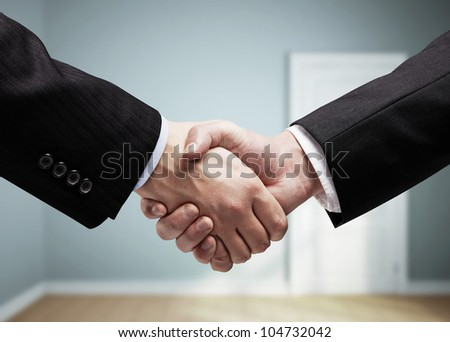 businessmen shaking hands on background of blue room - stock photo
