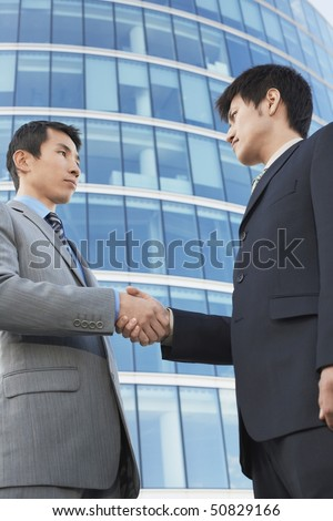 Businessmen Shaking Hands outside office building, low angle view