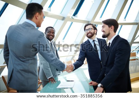 Businessmen shaking hands to confirm a deal - stock photo