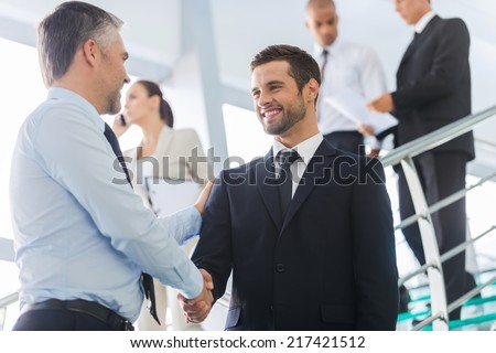 Businessmen shaking hands. Two confident businessmen shaking hands and smiling while standing at the staircase together with people in the background  - stock photo