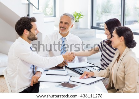 Businessmen shaking hands with businesswomen in the office