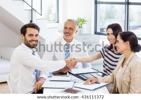Businessmen shaking hands with businesswomen in the office - stock photo