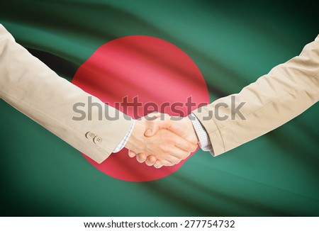 Businessmen shaking hands with flag on background - Bangladesh - stock photo