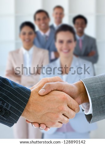 Businessmen shaking hands with smiling business team behind them