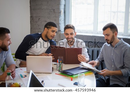 Businessmen sitting round table in board room in office. Happy men looking at documents while sitting in front of laptop computer.