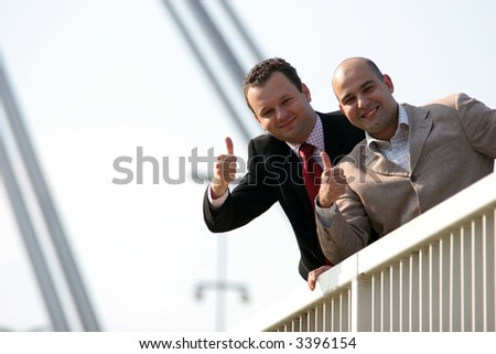 Businessmen standing on bridge and holding thumbs up - stock photo