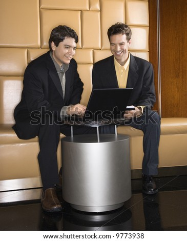 Businessmen talking and viewing laptop computer.