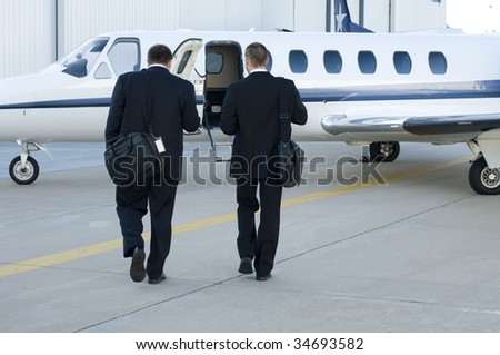 Businessmen talking and walking towards their corporate jet - stock photo
