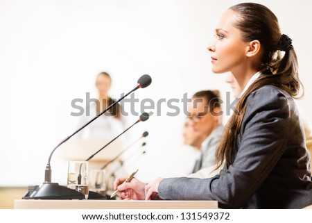 businessmen talking at the conference, sitting at the table, on the table microphones and documemts - stock photo