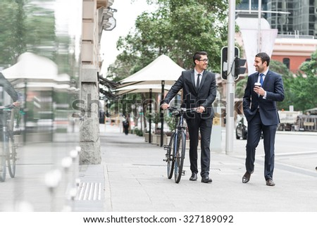 Businessmen talking while walking with bicycle outdoors - stock photo