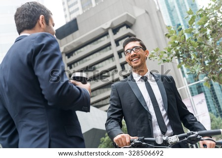Businessmen talking while walking with bicycle outdoors