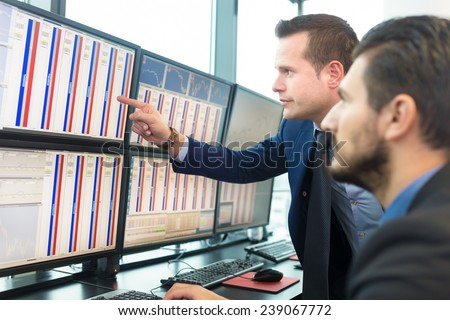 Businessmen trading stocks. Stock traders looking at graphs, indexes and numbers on multiple computer screens. Colleagues in discussion in traders office.  - stock photo