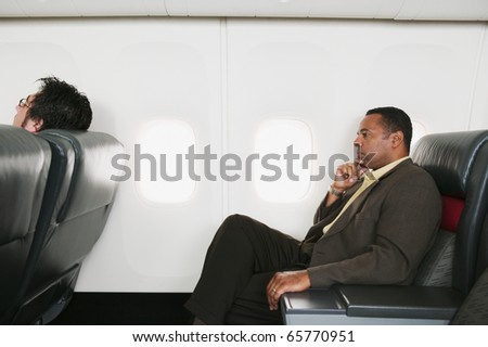 Businessmen traveling in an airplane - stock photo