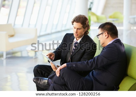 Businessmen With Digital Tablet Sitting In Modern Office - stock photo