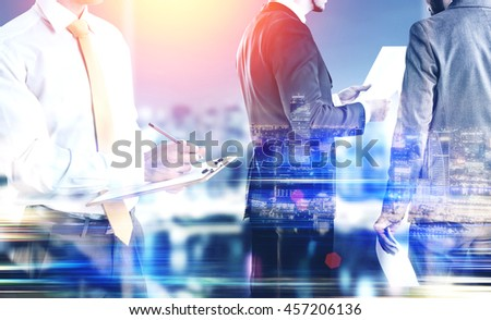 Businessmen working on illuminated night city background with abstract sunlight. Teamwork and partnership concept. Double exposure - stock photo