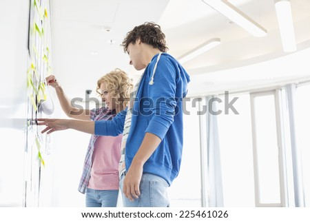 Businesspeople analyzing document stuck on wall in creative office - stock photo