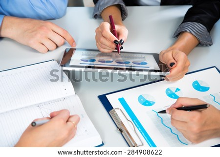 Businesspeople analyzing financial data in office - stock photo