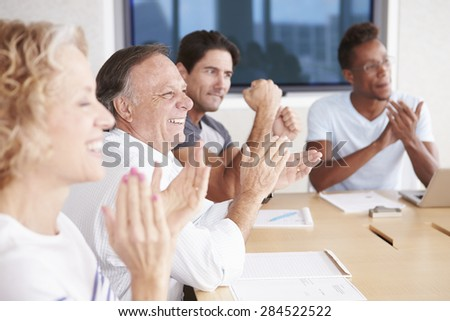 Businesspeople Applauding Colleague In Boardroom - stock photo