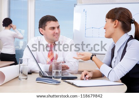 businesspeople are discussing in the office behind a desk with a laptop - stock photo