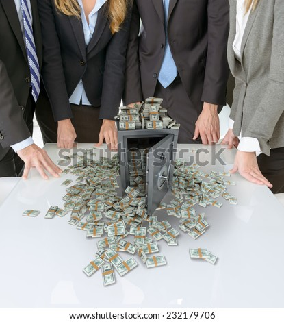 businesspeople around a table with a safe and piles of cash - stock photo