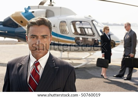 Businesspeople by helicopter - stock photo