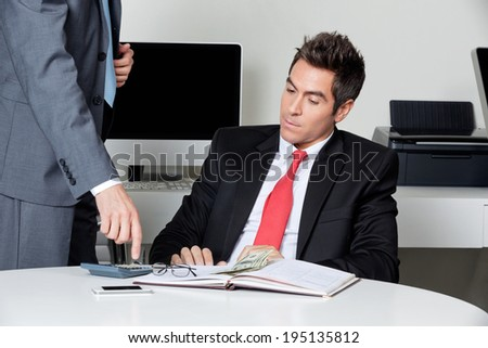 Businesspeople calculating finances at desk in office - stock photo