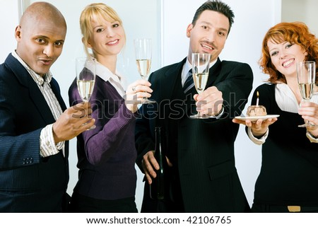 Businesspeople celebrating something in the office - a success or simply a birthday of a colleague - stock photo