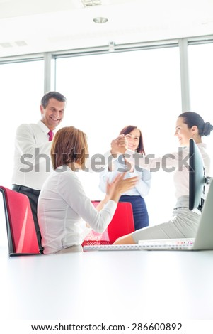 Businesspeople celebrating success in office - stock photo
