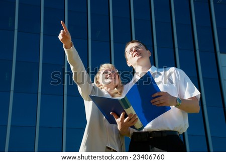 businesspeople discussing a project near a office building - stock photo