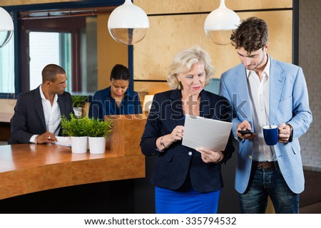 Businesspeople discussing on paperwork while receptionists working at counter in office - stock photo