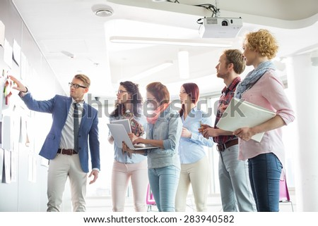 Businesspeople discussing over documents on wall in creative office - stock photo