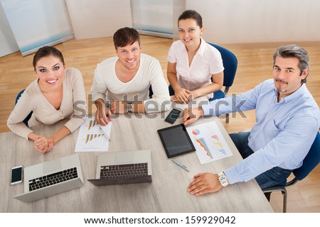 Businesspeople Discussing Work With His Colleagues At Workplace - stock photo