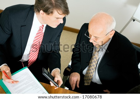Businesspeople discussion a business proposal, crunching some numbers - stock photo