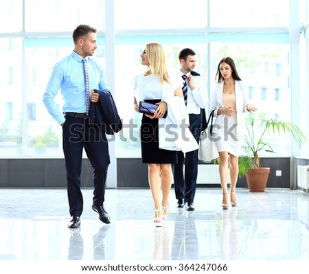 businesspeople group walking at modern bright office interior - stock photo