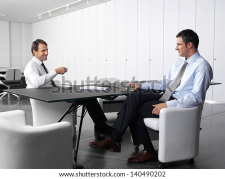 businesspeople having a business meeting at coffee table in office lobby
