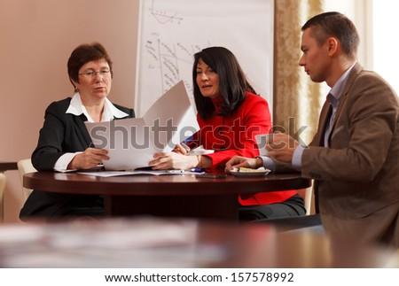 Businesspeople having a meeting over coffee sitting together at a table discussing a document, young man and two middle-aged women present - stock photo