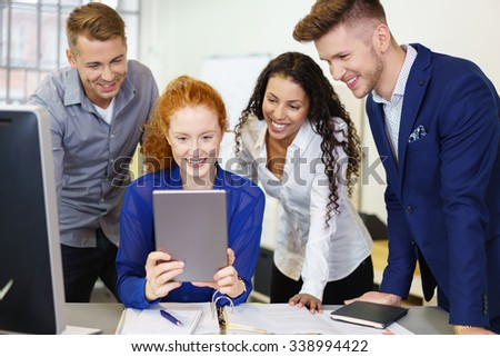 businesspeople having fun looking at tablet as they are sitting at the office - stock photo